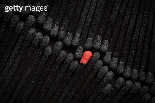 Group of Black Burnt and Used Matches with A Red New Match Standing Out Of Crowd. - gettyimageskorea