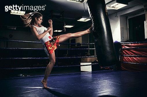 Female muay thai fighter training with a punching bag - gettyimageskorea