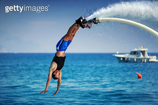 Closeup side view of a young man enjoying flyboarding session at sea on a sunny summer day. He's making a dive into the water. - gettyimageskorea