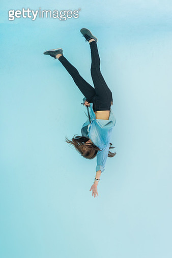 Low Angle View Of Woman Falling Against Blue Sky - gettyimageskorea