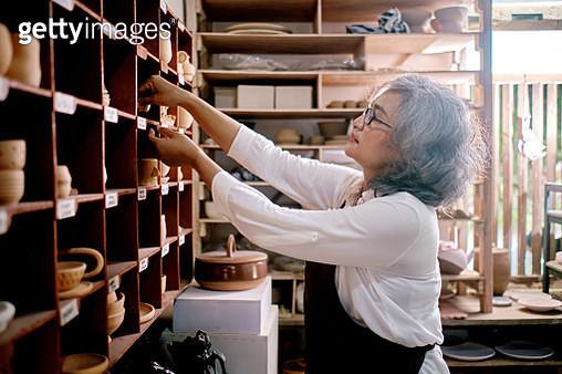 Mid Women Working on Making Clay Objects in Pottery Workshop - gettyimageskorea