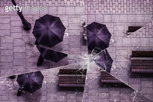 Broken glass of the guy walking under the rain with black umbrella. - gettyimageskorea