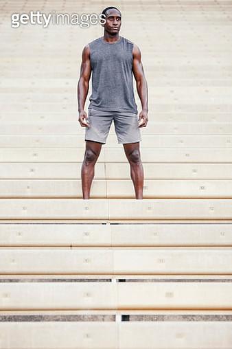 Portrait of man standing on bleachers in empty stadium - gettyimageskorea