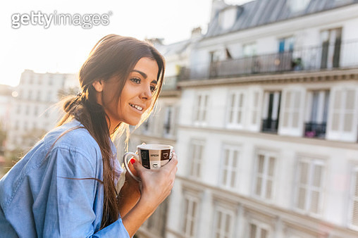 Young woman standing on balcony, holding cup of coffee - gettyimageskorea