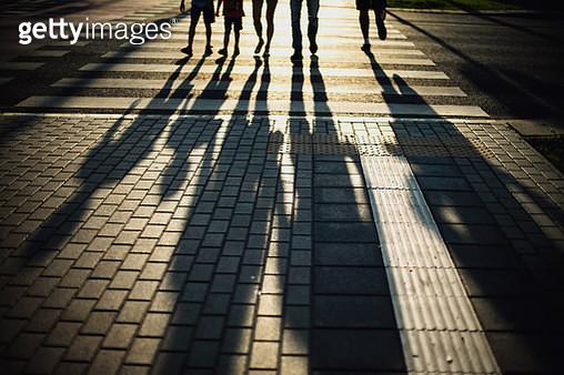 Low Section Of Silhouette People Walking On Zebra Crossing - gettyimageskorea