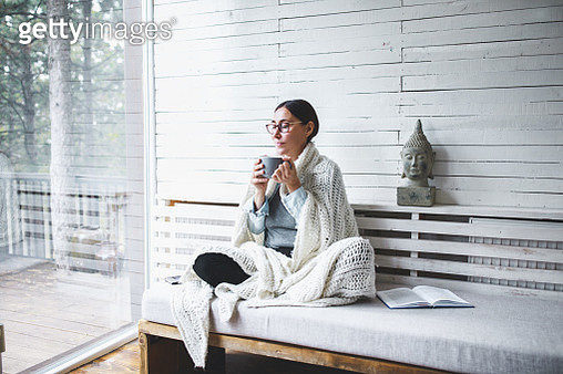 Middle-aged woman siting comfortable and enjoys tea - gettyimageskorea