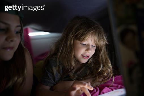 Girl friends using digital tablet in dark fort, enjoying sleepover - gettyimageskorea