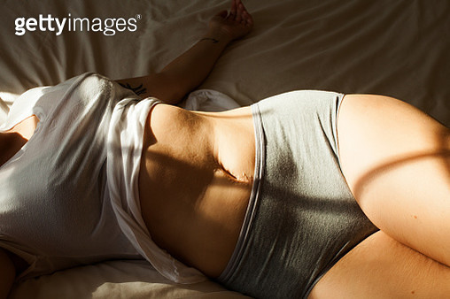 A young woman's torso lying on a bed in sunlight - gettyimageskorea