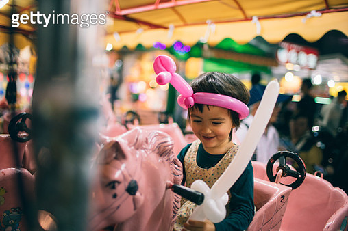 Little girl enjoying merry-go-round at Taiwanese night market - gettyimageskorea