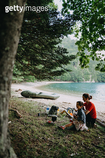 Mother and child having break on secluded lake beach during kayaking adventure - gettyimageskorea