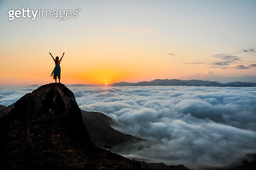Woman enjoys on top of a cliff above the sea of clouds at sunset. - gettyimageskorea
