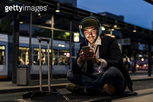 Young man in the city with headphones and cell phone in the evening - gettyimageskorea