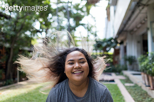 Portrait of Happy Young Mixed Race Woman With Hair Blowing - gettyimageskorea