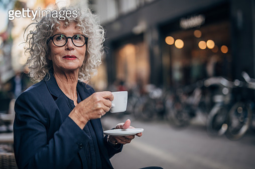 One woman, modern mature lady with gray hair, drinking coffee in sidewalk cafe. - gettyimageskorea