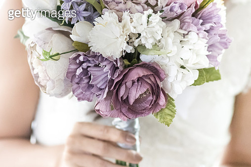 Midsection Of Bride Holding Bouquet While Standing Against White Background - gettyimageskorea