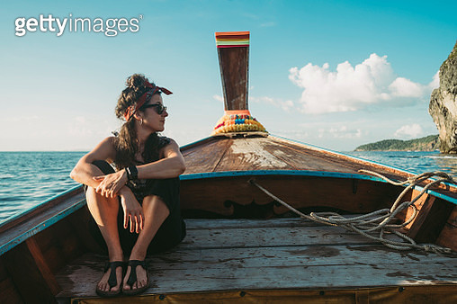 Young woman on a longtail boat in Thailand during sunset, Phi Phi Island - gettyimageskorea