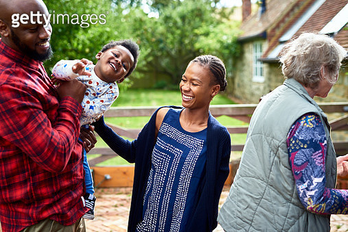 Father holding cute boy with mother laughing, visiting family in rural setting, togetherness, weekend, social gathering - gettyimageskorea
