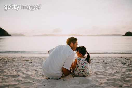 Rear view of father kissing his preschool daughter on beach at sunset, Kerama Islands National Park, Okinawa, Japan - gettyimageskorea