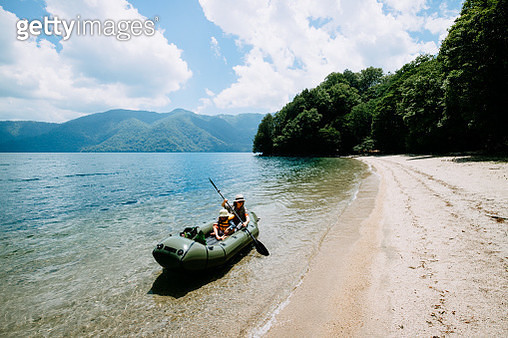 Mother and child paddling inflatable raft along beach, Lake Chuzenji, Nikko, Japan - gettyimageskorea