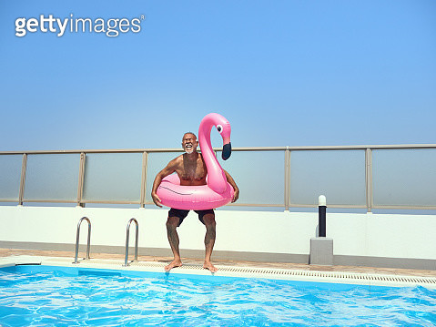Senior man jumping into the pool with a pink swan-shaped float. - gettyimageskorea
