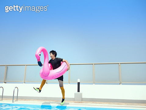Young male jumping into pool with inflatable pool toy - gettyimageskorea