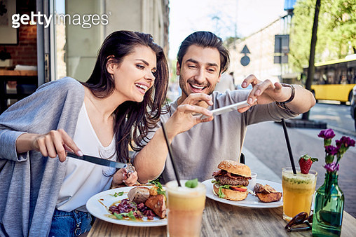 Happy young couple taking photo of food at outdoors restaurant - gettyimageskorea