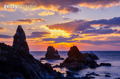 Rock Formation In Sea Against Sky During Sunset - gettyimageskorea