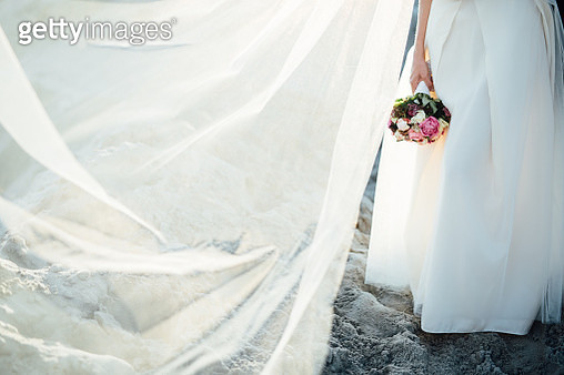 Low Section Of Woman Holding Bouquet At Beach - gettyimageskorea