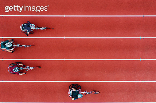 View from directly above four women racing in wheelchairs at a track and field event - gettyimageskorea
