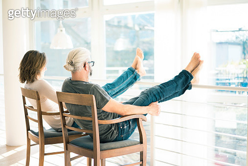 Relaxed mature couple sitting on chairs at home with feet up - gettyimageskorea