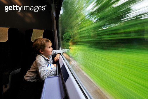 Boy looking out of train window - gettyimageskorea