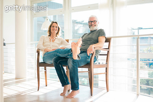 Portrait of relaxed mature couple sitting on chairs at home - gettyimageskorea