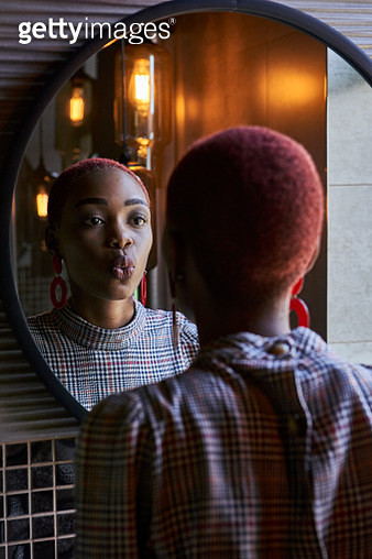 Young woman with short haircut looking to her reflection and sending a kiss in a round mirror - gettyimageskorea