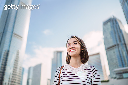 Young Asian woman looking away joyfully in business district - gettyimageskorea