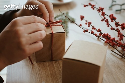Cropped Hands Of Person Tying Small Cardboard Box On Table - gettyimageskorea