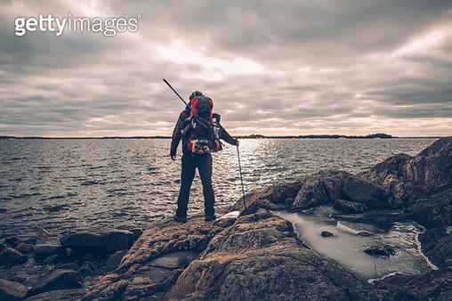 Sweden, Sodermanland, backpacker standing at the seashore under cloudy sky - gettyimageskorea
