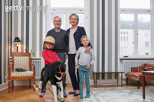 Grandparents and grandchildren with rocking horse in living room - gettyimageskorea