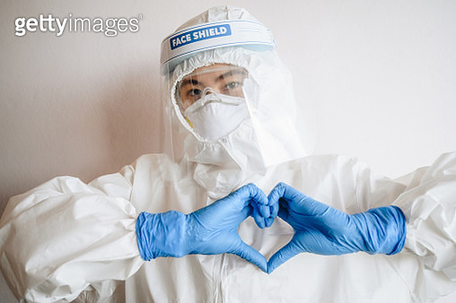 Healthcare worker doing a heart gesture with her fingers in front of her chest showing her love and affection while wearing PPE suit for working in hospital. - gettyimageskorea