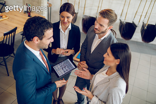 Four business people discussing business strategy using digital tablet - gettyimageskorea