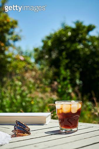 Summer Garden scene, Glass of black Iced Coffee on a garden table in bright sunshine. - gettyimageskorea