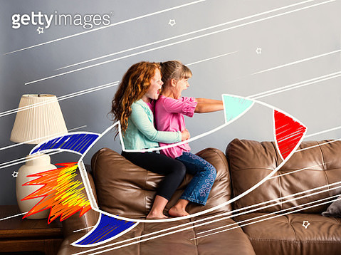 7 and 9 year old sisters sitting on a sofa pretending to be riding in a rocketship - gettyimageskorea