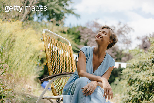 Relaxed woman sitting in garden on chair with closed eyes - gettyimageskorea