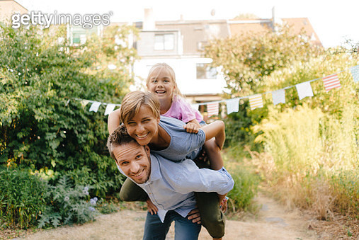 Happy father carrying family piggyback in garden - gettyimageskorea