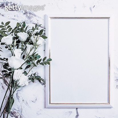 Blank photo frame and pink flowers over marble table background. Women Day. Mockup. Flat lay, top view - gettyimageskorea