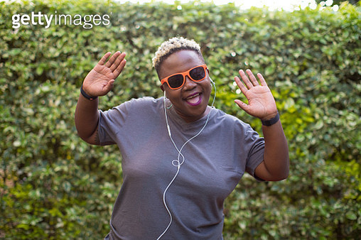 Portrait of a black woman listening to music outside with hands in the air - gettyimageskorea
