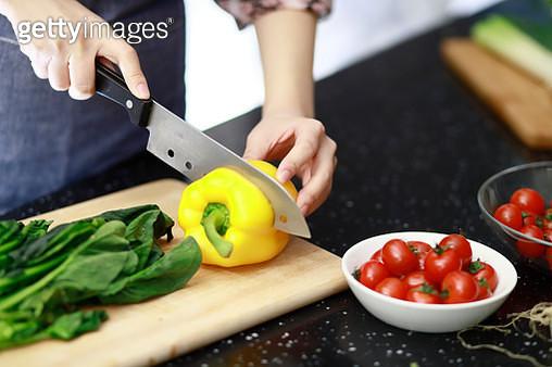 Woman cutting vegetables in kitchen - gettyimageskorea