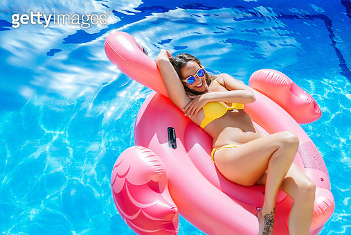 Carefree young woman on pink flamingo float in swimming pool - gettyimageskorea