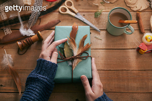 Woman decorating Christmas present with leaf and feathers, close-up - gettyimageskorea
