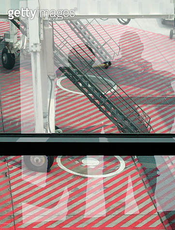 Reflections of People in Window Looking Down at Airport Loading Area - gettyimageskorea