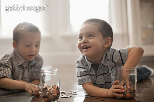 Two children playing with coins, dropping them into glass jars. - gettyimageskorea